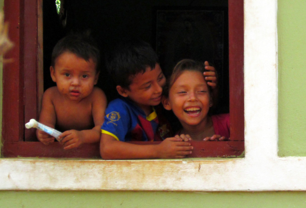 Adriana, at the window of her home with her two little brothers, Brian and Andi